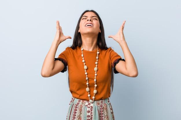 Mulher árabe nova que grita ao céu, olhando acima, frustrado.