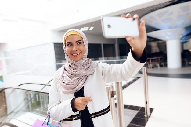 Mulher árabe nova que toma selfie na alameda moderna.