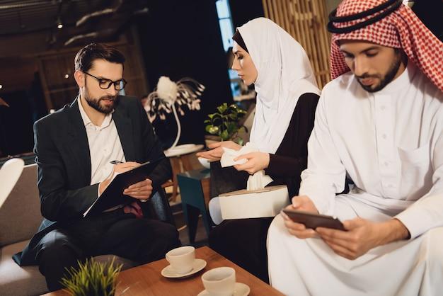 Mulher árabe responde a perguntas do psicólogo.