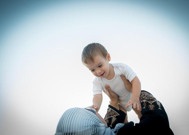 Mulher árabe segurando bebê no ar e brincando