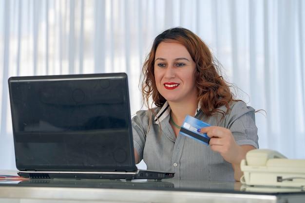 Mulher árabe segurando o cartão de crédito e usando o laptop. compras online