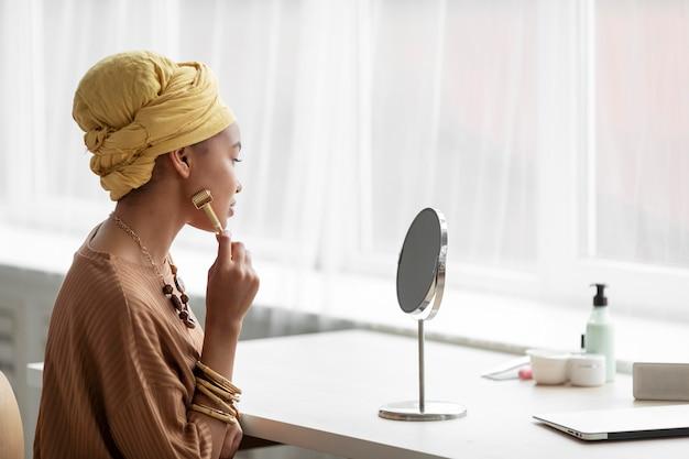 Mulher árabe usando um massageador facial. tratamento de beleza