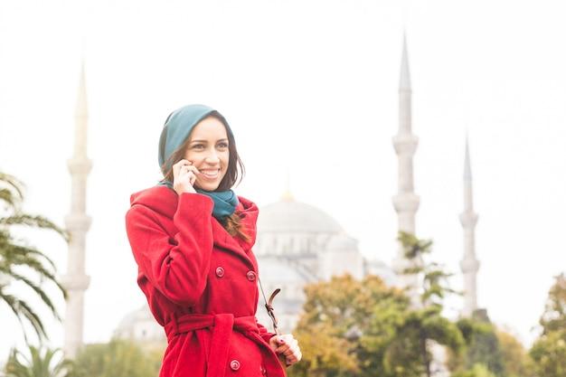 Mulher árabe usando véu na frente de uma mesquita em istambul