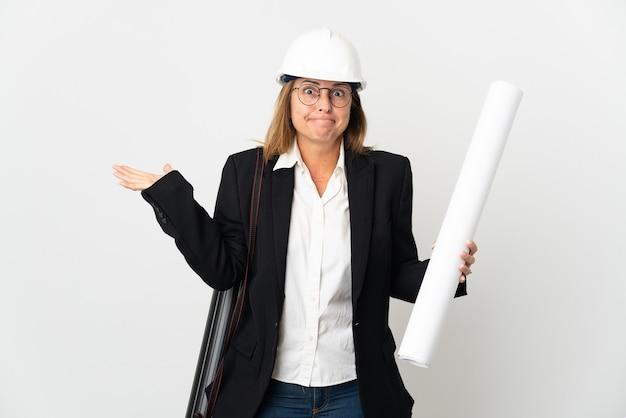 Mulher arquiteta de meia-idade com capacete e segurando plantas na parede isolada, tendo dúvidas enquanto levanta as mãos