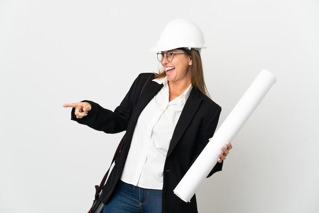 Mulher arquiteta de meia-idade com capacete e segurando plantas sobre fundo isolado apontando o dedo para o lado e apresentando um produto