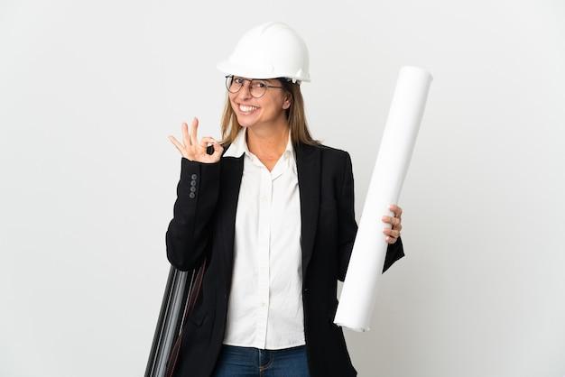 Mulher arquiteta de meia-idade com capacete e segurando plantas sobre fundo isolado, mostrando sinal de ok com os dedos