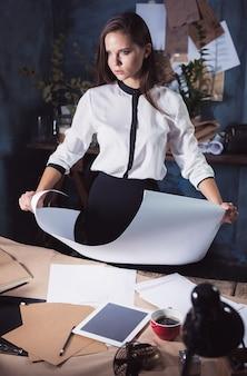 Mulher arquiteta trabalhando na mesa de desenho no escritório ou em casa. foto de estúdio