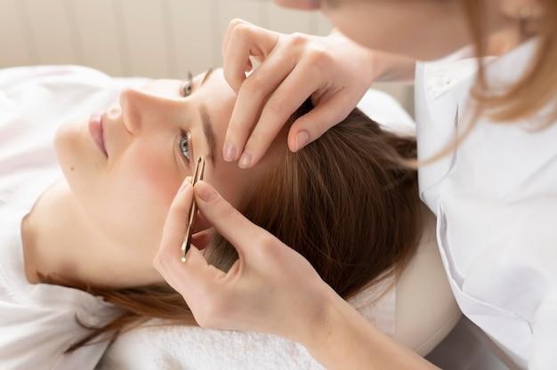 Mulher arrancando as sobrancelhas de uma cliente em um salão de beleza