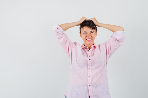 Mulher arrancando o cabelo na camisa rosa e parecendo frustrada, vista frontal.