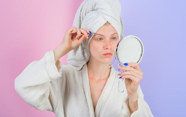 Mulher arrancar sobrancelhas olhando no espelho depilar sobrancelhas processo de maquiagem sobrancelhas conceito de cuidados de beleza