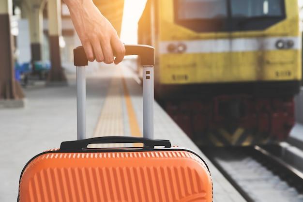 Mulher arrastando mala laranja bagagem saco, andando na estação de trem.