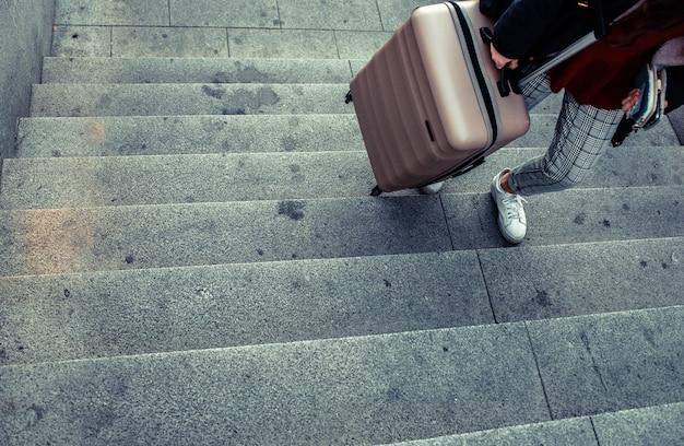 Mulher arrastando uma mala de carrinho para subir as escadas de um metrô.