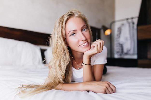 Mulher arrepiante com grandes olhos azuis, descansando em casa. modelo feminino com pele bronzeada, deitada na cama com uma expressão de rosto feliz.