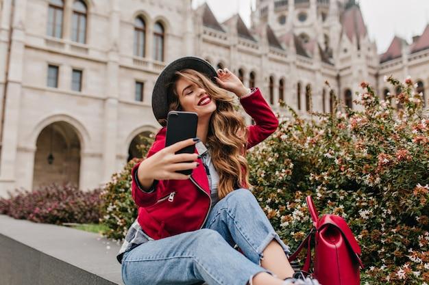 Mulher arrepiante em jeans retrô fazendo selfie com os olhos fechados perto das flores da rua