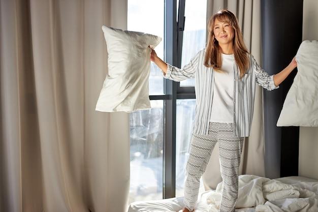 Mulher arruma a cama com alegria, segura os travesseiros nas mãos e sorri, vestindo roupas de casa, pela manhã