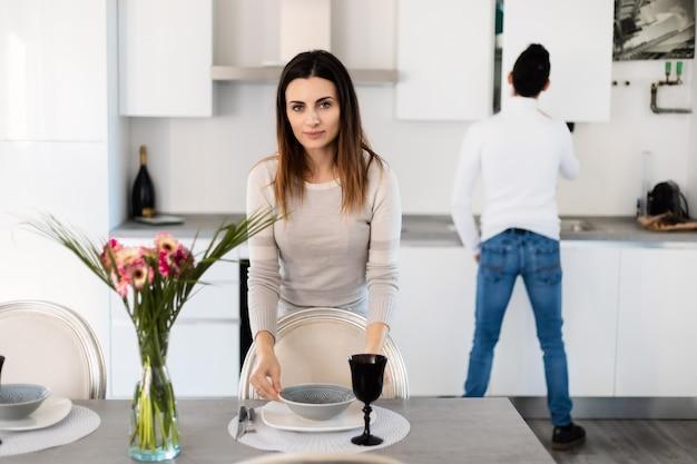 Mulher arrumando a mesa enquanto o namorado está cozinhando