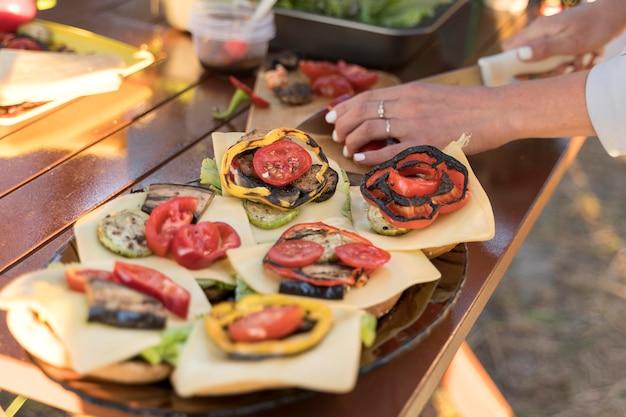 Mulher arrumando comida deliciosa na mesa para amigos
