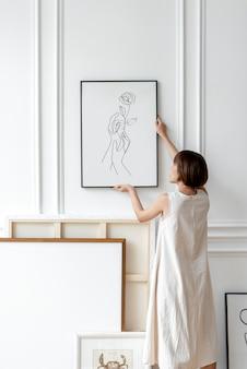 Mulher arrumando moldura em uma parede em uma sala de decoração japonesa