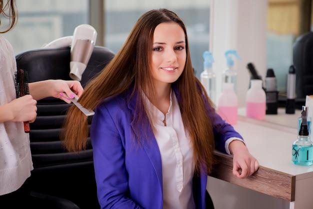 Mulher arrumando o cabelo feito em salão de beleza