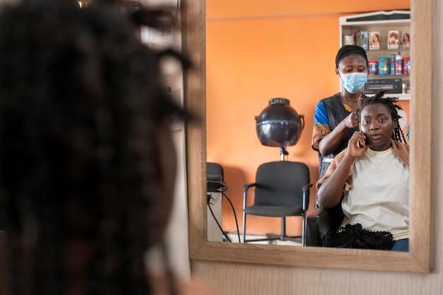Mulher arrumando o cabelo no salão