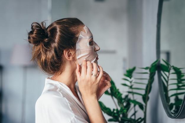 Mulher arrumando o rosto no banheiro com uma máscara no rosto na frente do espelho.
