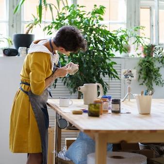Mulher artesã ceramista gravar master class para cursos on-line em vídeo de cerâmica em oficinas de fabricação de jarros