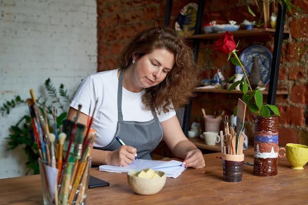 Mulher artesã escrevendo no caderno e planejando