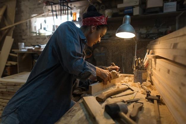 Mulher artesã trabalha em uma oficina de madeira. conceito artesanal