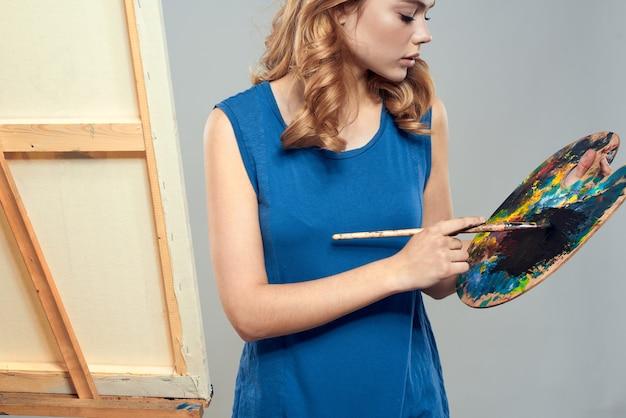 Mulher artista boina azul desenho paleta cavalete arte passatempo creative. foto de alta qualidade