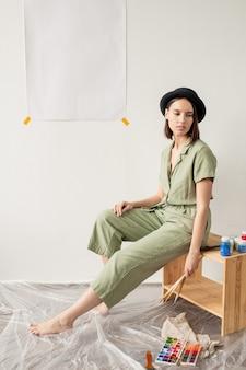 Mulher artista com pincéis e tela em branco