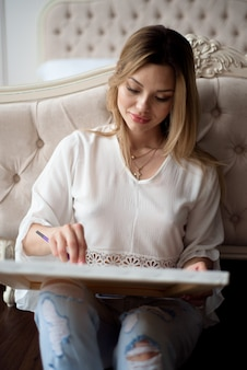 Mulher artista desenhando sua foto na tela com cores de óleo em casa