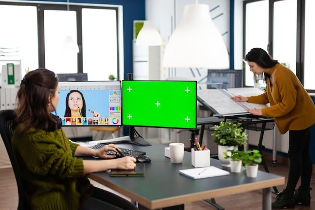 Mulher artista digital trabalhando na edição de fotos criativas usando tela isolada de croma de tela verde
