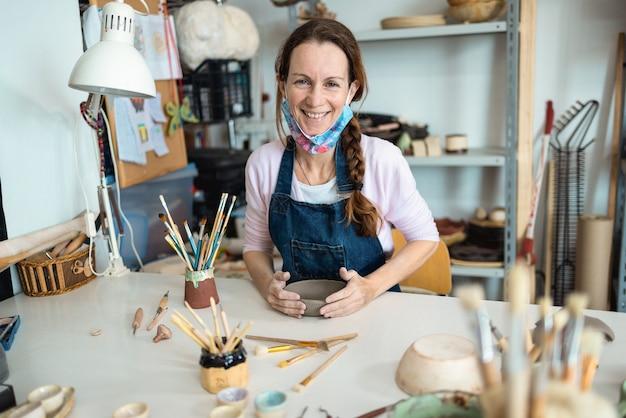 Mulher artista feliz moldando com argila na oficina de cerâmica
