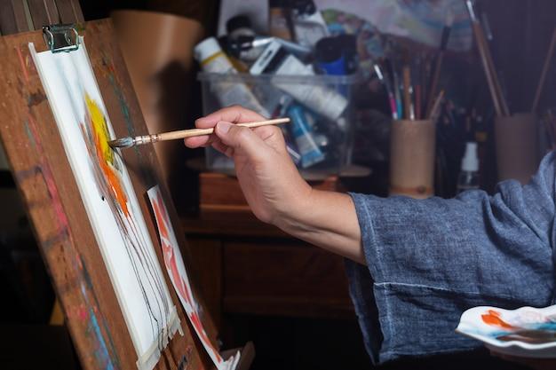 Mulher artista pinta desenho em aquarela no cavalete Foto Premium