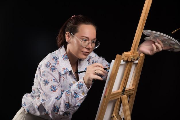 Mulher artista pinta um quadro em tela com lápis sobre fundo preto