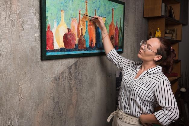 Mulher artista pinta um quadro em tela com pincel em fundo de mármore