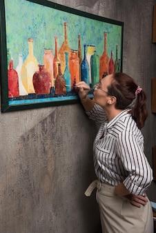 Mulher artista pinta um quadro em tela com pincel em mármore