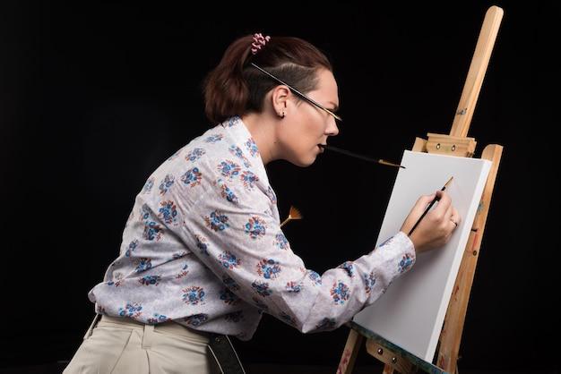Mulher artista pinta um quadro em tela com pincel no preto