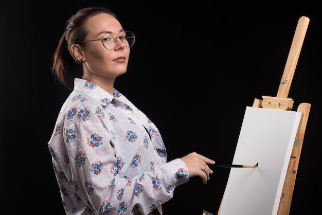 Mulher artista pinta um quadro na tela com lápis no preto