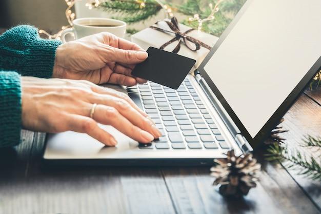 Mulher às compras com cartão de crédito pelo laptop no interior de casa.