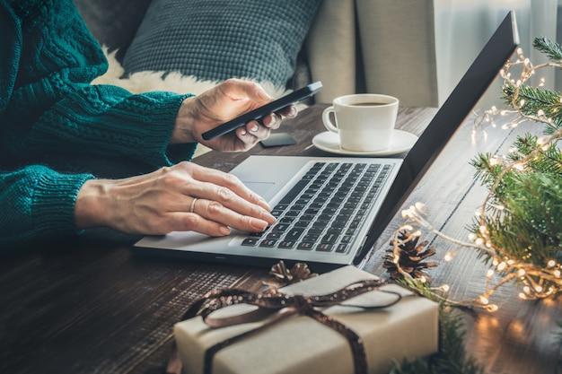 Mulher às compras com smartphone pelo laptop no interior de casa.
