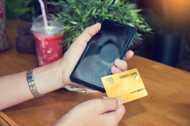 Mulher às compras na internet com smartphone e cartão de crédito