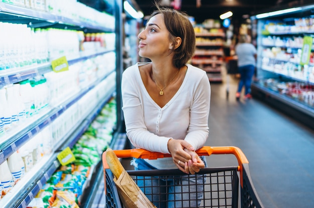Mulher às compras na mercearia, na geladeira
