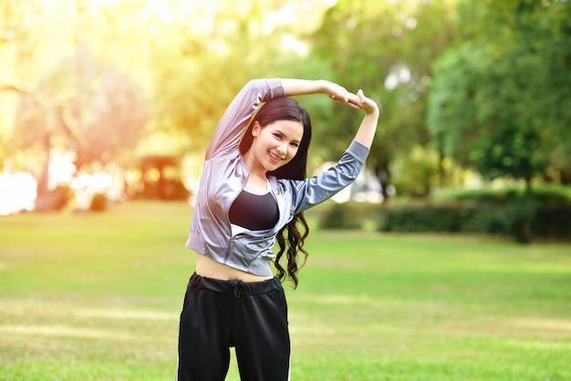 Mulher ásia manter o exercício do corpo em forma esticar os músculos para a saúde no jardim