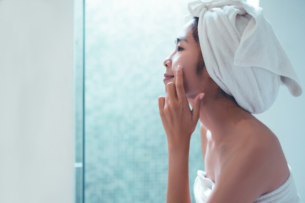 Mulher asian, aplicando, loção rosto