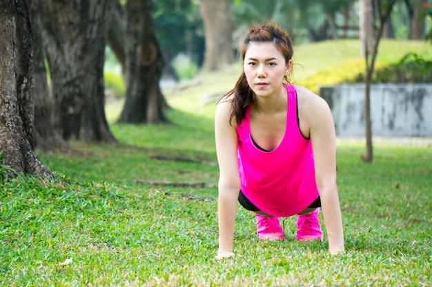 Mulher asian, aquecer, para, exercício, por, peso peso, pushup, ligado, verde, gramados, parque