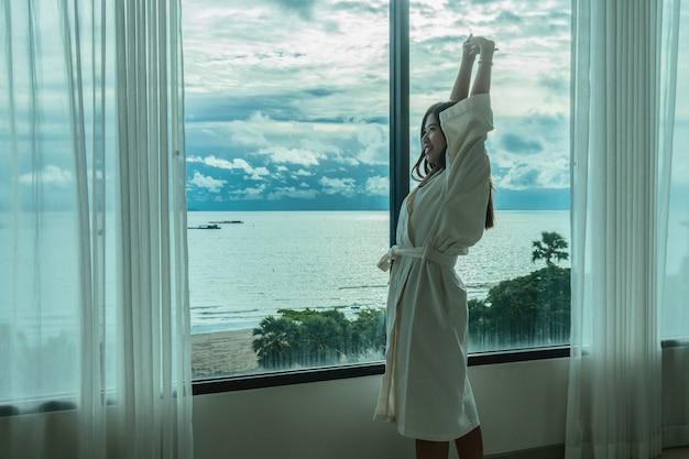 Mulher asian, em, bathrobe, paleto, estiramento, oneself, e, sightseeing, a, praia mar, quando, acordar
