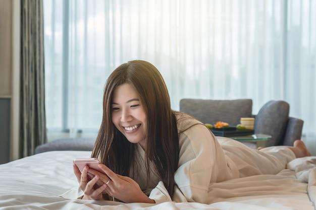 Mulher asian, em, bathrope, paleto, usando, a, esperto, telefone móvel, com, sorrindo, ação