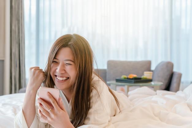 Mulher asian, em, bathrope, paleto, usando, a, esperto, telefone móvel, com, sucesso, ação, cama