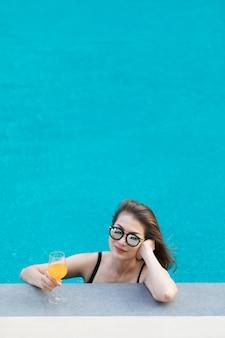 Mulher asian, em, piscina, com, vidro suco laranja